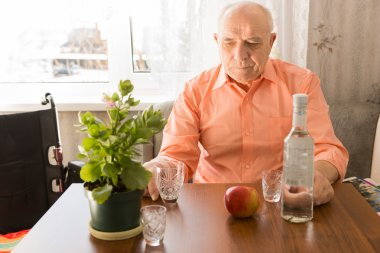 Lonely Elderly Drinking Wine at the Wooden Table