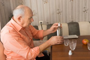Old Man Holding a Bottle of Wine on the Table