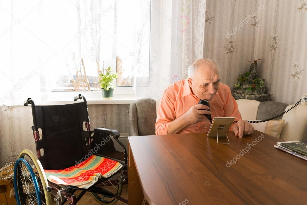 Elderly Man Shaving his Beards at the Living Room