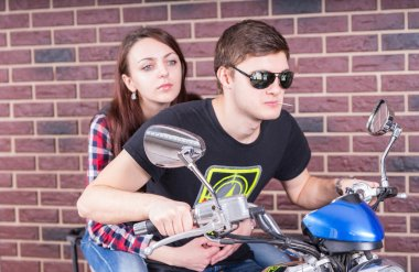 Young Couple on Motorcycle in front of Brick Wall