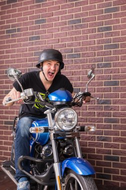 Young man shouting as he speeds on his motorbike