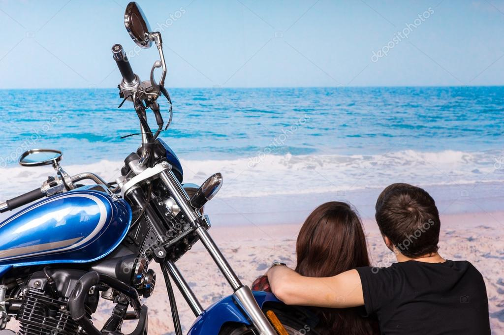 Romantic couple at the beach with their motorbike