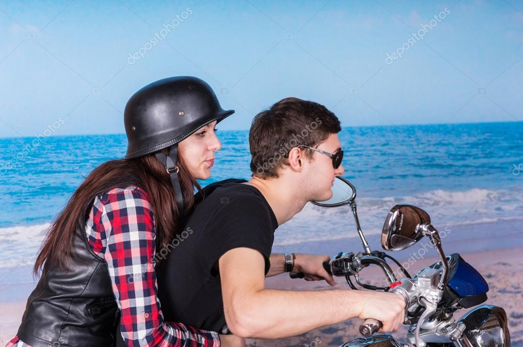 Young Couple Riding Motorcycle on Beach