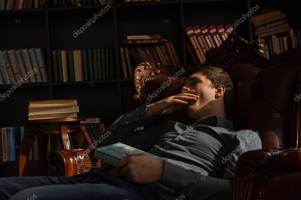 Young Man Slouching And Yawning On The Chair Stock Photo