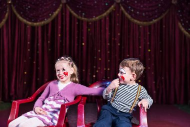 Young Clowns Sitting and Laughing on Stage
