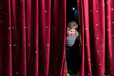Anxious young actor looking out from the curtains