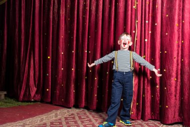 Adorable little boy singing on stage during a play