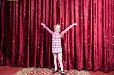Little girl standing on stage during a performance