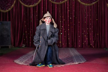 Boy wearing retro coat and Russian hat on stage