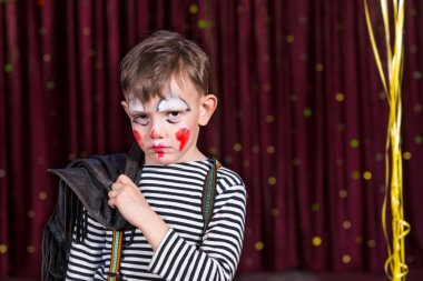 Sulky little boy wearing face paint on stage