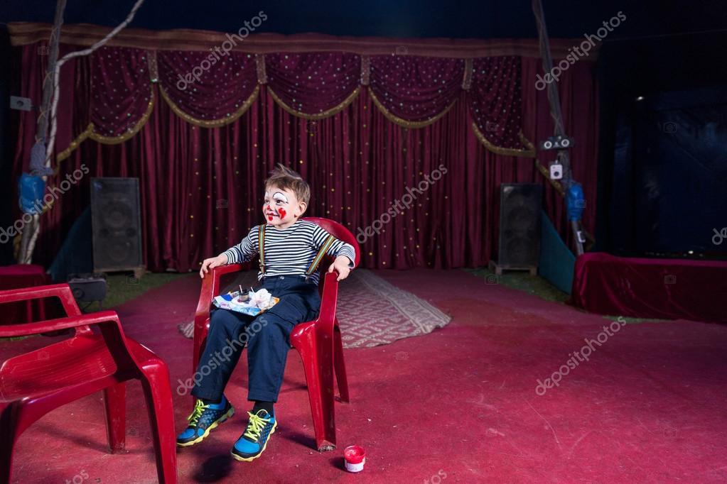 Make Up Stoel : Jongen het dragen van make up van de clown zittend in stoel op het