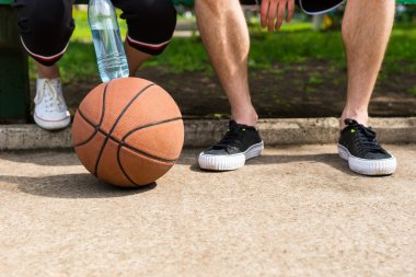 Basketball at Feet of Couple Sitting on Park Bench