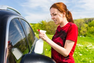 Woman Cleaning Car Windows with Spray Cleaner