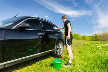 Man Washing Car in Field on Sunny Day