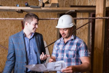 Architect and Foreman Inspecting Building Plans