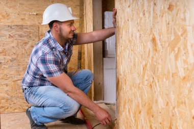 Builder Measuring Door Frame In Unfinished Home