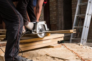Men Using Power Saw to Cut Planks of Wood