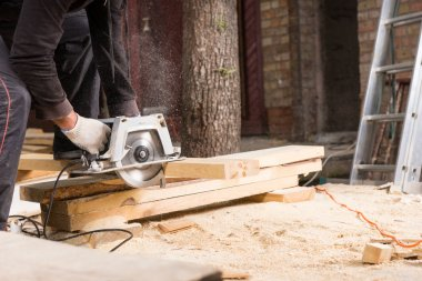 Man Using Power Saw to Cut Planks of Wood
