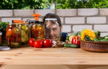 Girl Peering Through Empty Glass Jar in Garden