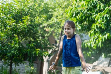 Young Girl Cooling Off in Sprinkler on Summer Day
