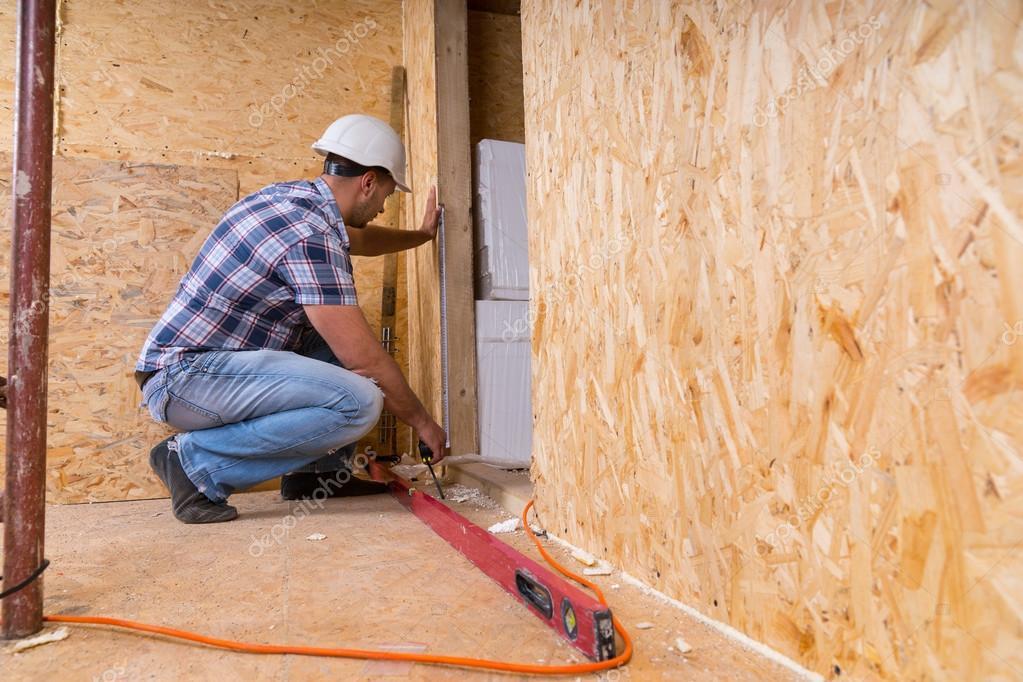 Builder Measuring Door Frame In Unfinished Home