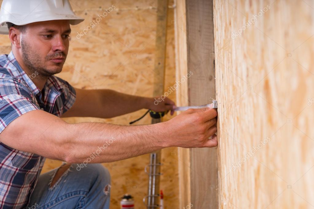 Trabajador de la construcción, medición de anchura de marco de ...