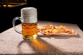 Džbánek piva a plátky pizzy na prkénku