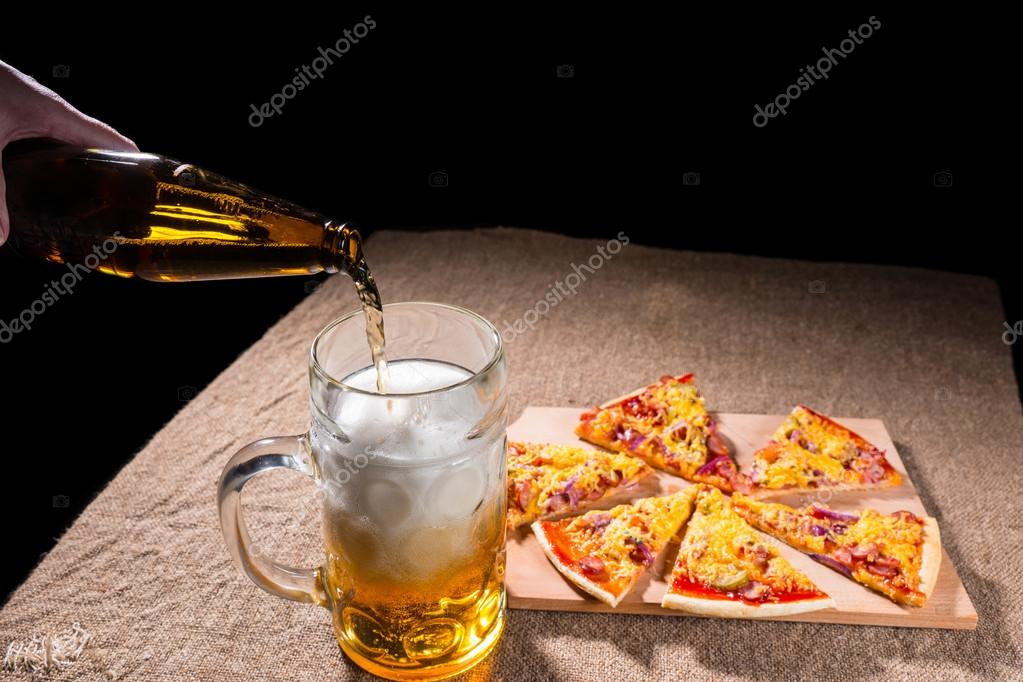 Pouring Beer into Glass next to Pizza Slices