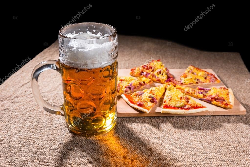 Mug of Beer and Slices of Pizza on Cutting Board