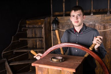 Young Man Steering Wooden Antique Ship