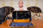 Fotografia Serious Old Man Behind a Sewing Machine Case