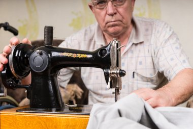 Senior Man Using Old Fashioned Sewing Machine