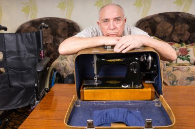 Sad Old Man Leaning on a Sewing Machine in a Case