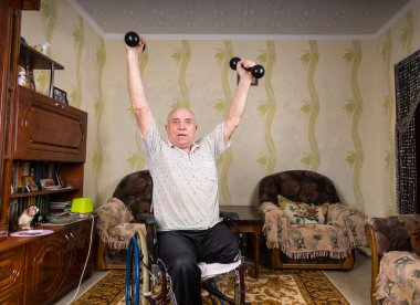 Invalid old man puts his hands up with dumbbells