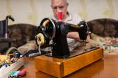 Fotografia Senior Man with Vintage Sewing Machine at Home