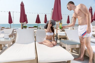 Man Serving Drink to Woman on Deck of Beach Resort