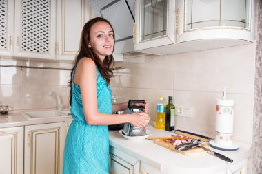 Pretty young woman standing cooking in her kitchen