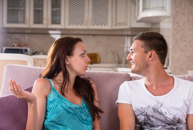 Young Couple Having Conversation on Sofa at Home