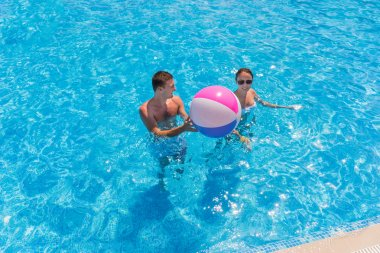 Young Couple in Swimming Pool with Beach Ball