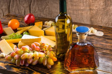Gourmet cheese platter with alcoholic beverages
