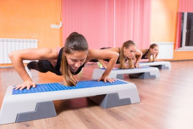 Group of Women Strengthening Cores in Step Class