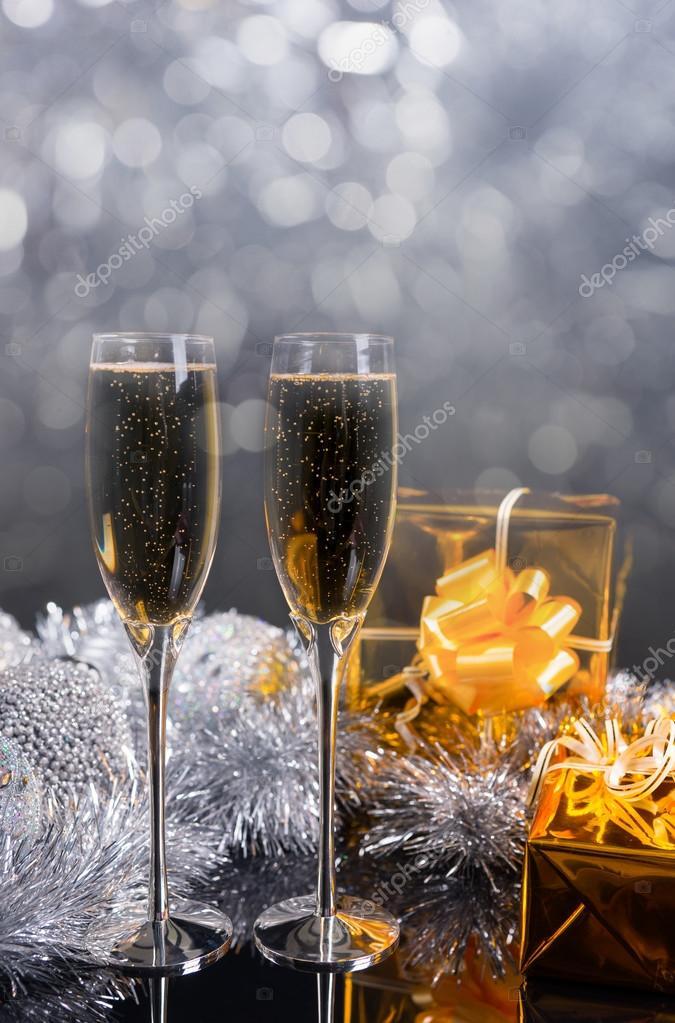 fd4cd56751add6 Champagne bril op tafel met gouden geschenken– stockafbeelding