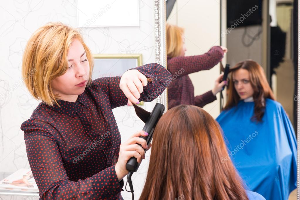 Stylist Using Flat Iron To Style Clients Hair Stock Photo