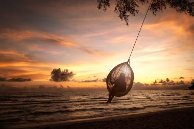 Silhouette woman on a beach swing