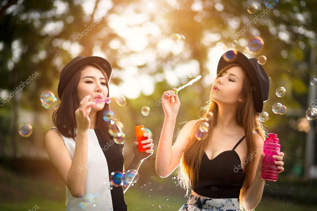 Beautiful asian teen girls blowing soap bubbles
