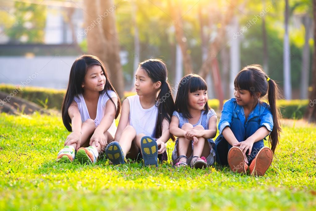 Four happy smiling child playing in park