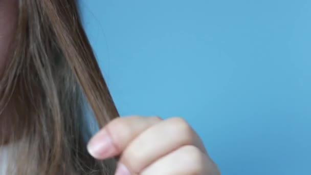 Girl holds strand of hair front view on blue background, hair loss concept
