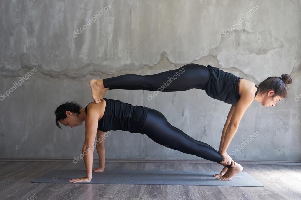 Dos mujeres practicando yoga pareja — Foto de Stock bbec83ea03af