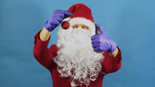 Muž jako Santa Claus v ochranných lékařských rukavicích a masce používá dezinfekční dezinfekční sprej na vánoční míč hračku. COVID Coronavirus a novoroční koncept. Pandemie. Modré pozadí