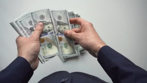 Man counts bundle of 100 american dollars money. Bribe and corruption concept. Finance and investment. Cash banknotes. Currency exchange of one hundred bills. Overhead top view. Rich business economy